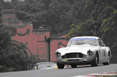 A white Aston Martin races over the hill.